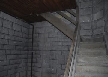 Stone staircase next to wooden hand rales