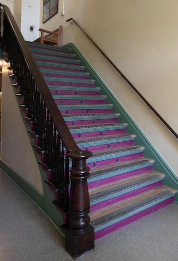 Purple staircase with wooden rails.