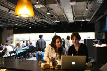 Two women confer in front of a laptop