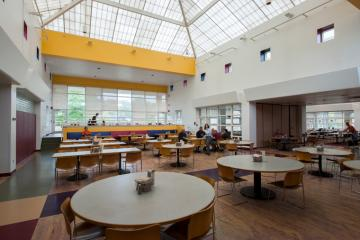 Interior of a dining hall with round tables and a skylight