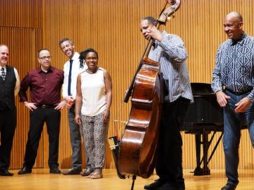 A professor demonstrates the double bass for a student