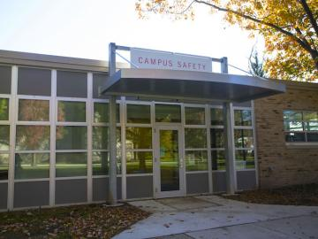 exterior view of campus safety building with big sign above the doorway.