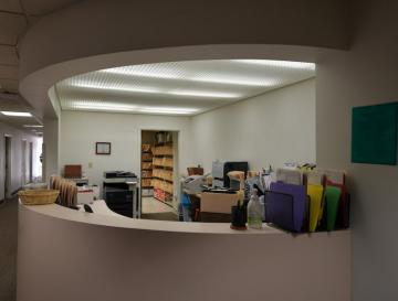 interior office space with large desk and files situated on top.