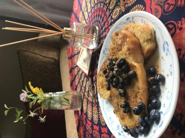French toast with blueberries on a tablecloth with vase of flowers in the background