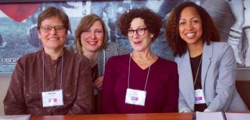 four woman professors standing next to one another.