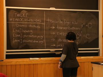 A woman writes on a large chalkboard.