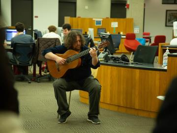 A man plays guitar in the library.
