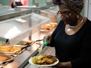 Visiting Chef Vel Scott dishing food at Afrikan Heritage House dining hall.