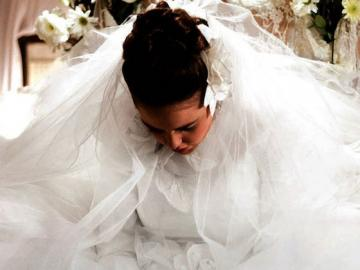 woman dressed in white wedding gown looking down.