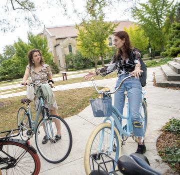 Two students with bikes outside talking.