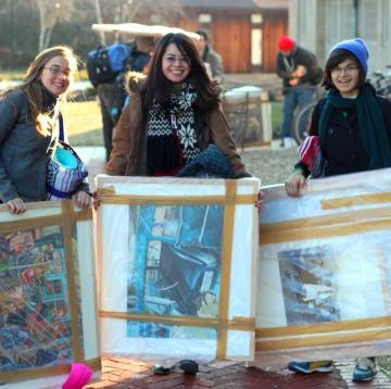 Three students stand with art they rented from the museum.
