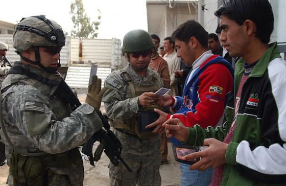 armed sosldiers checking identifcation cards of two men