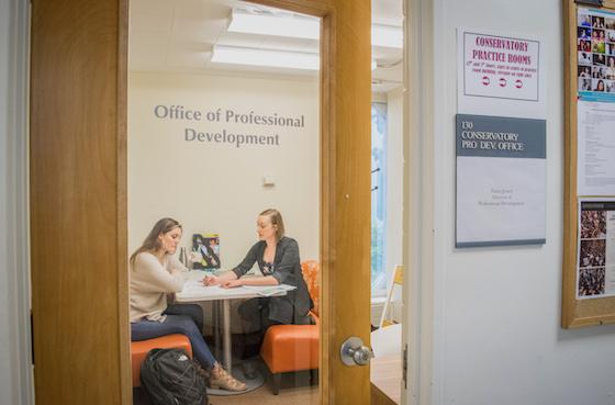 Two people have a discussion at a small table behind a glass door marked 'Office of Professional Development'