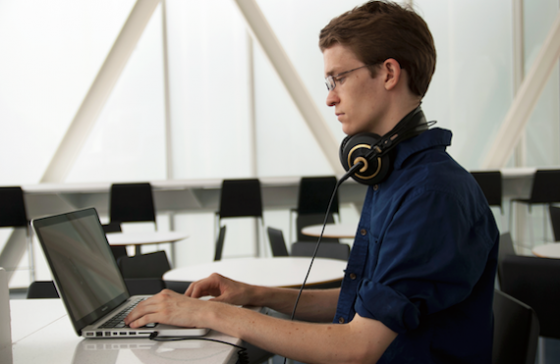 A student works on a laptop computer at a table, a pair of headphones resting around his neck