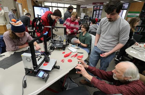 A crowd of people looks at items printed from a 3D printer.