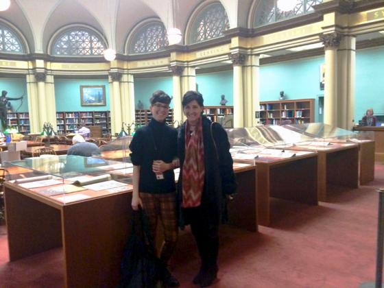 Two people in a library with documents displayed in glass cases