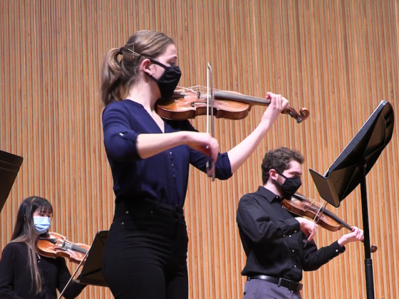 Baroque violinists performing onstage.