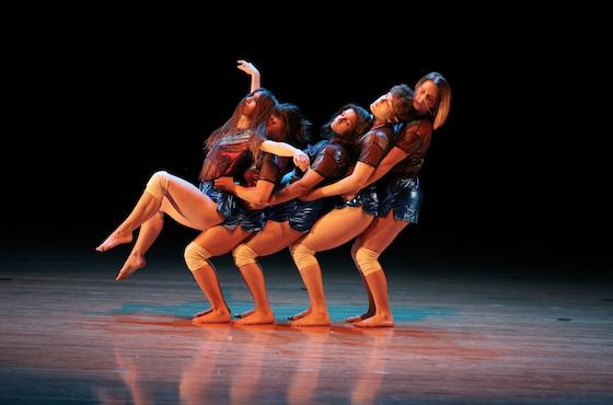 groups of dancers intertwined in a dance move on stage.
