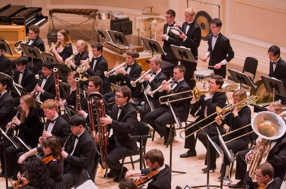 Oberlin Orchestra woodwinds and brass section during a performance in Carnegie Hall