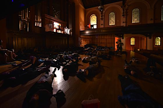 Under dim lighting in Finney Chapel, students lie on the stage beneath the pipe organ.