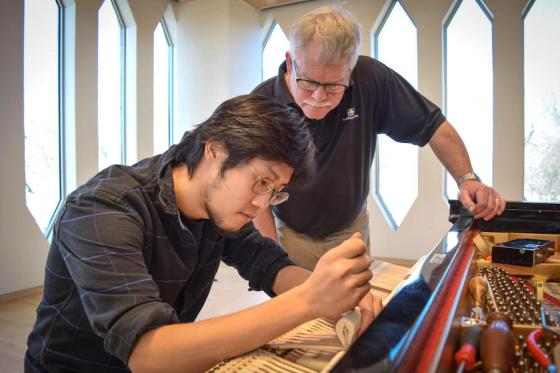 teacher John Cavanaugh works with a piano technology student
