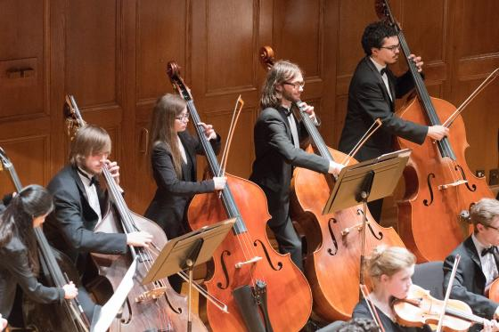 Five double bassists performing in an orchestra on the Finney Chapel stage.