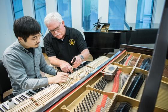 Student and instructor examine the key mechanism in a grand piano