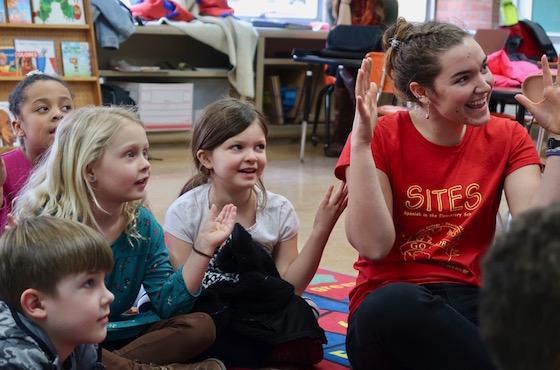 children sitting on floor with student teacher singing.