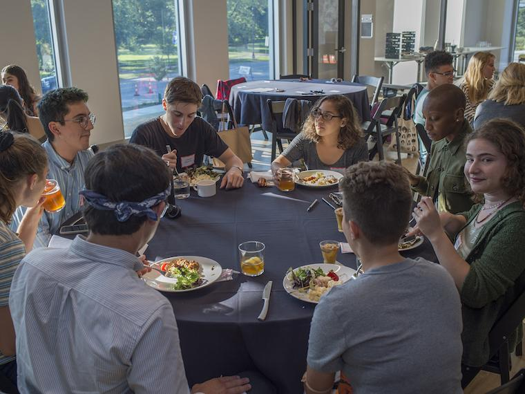 group of students sitting around a table eating dinner.