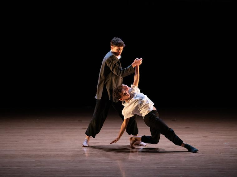 two people on stage doing a dance move; one upright, the other on the floor.