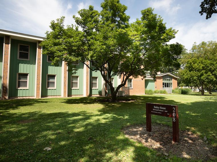 a single story residence hall with sign in front.