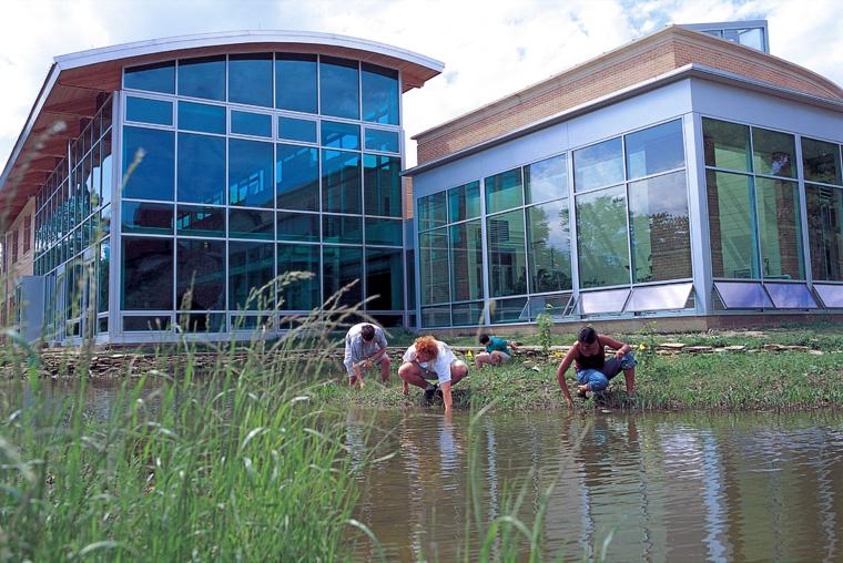 Students crouch at the edge of the pond behind  the Adam Joseph Lewis Center.