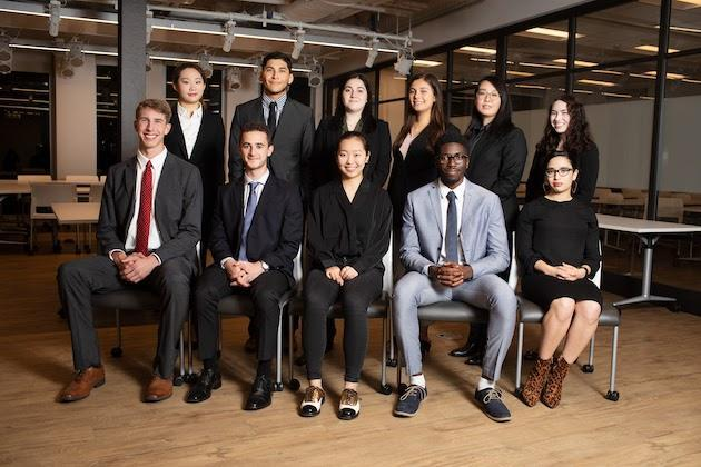 Eleven students in business attire are posed for a group photo in an office setting.