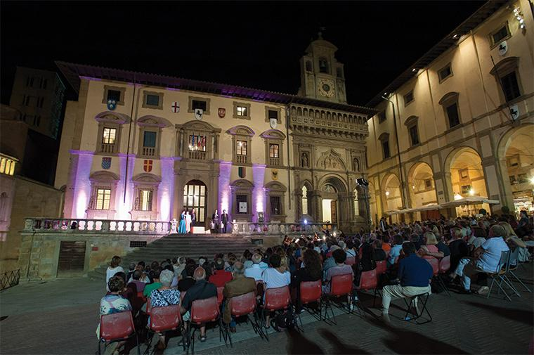 Performers on stone steps at night in front of an old Italian building