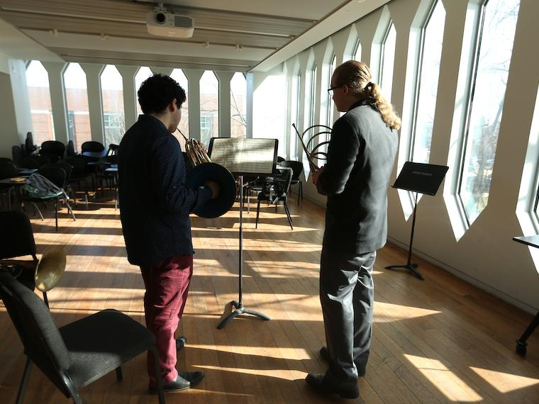 a student takes a horn lesson from a teacher in a large practice room.