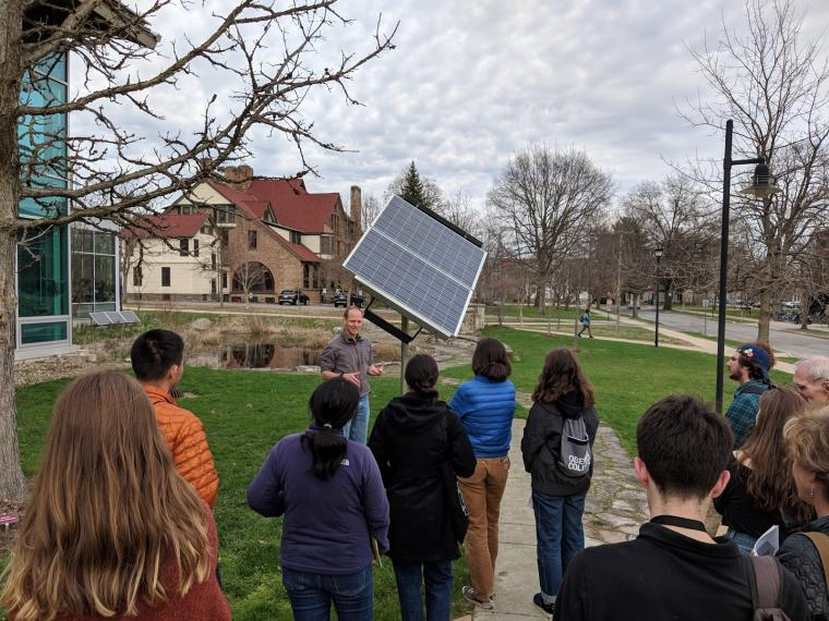 Professor John Petersen speaks to a class in front of the single mounted solar panel.