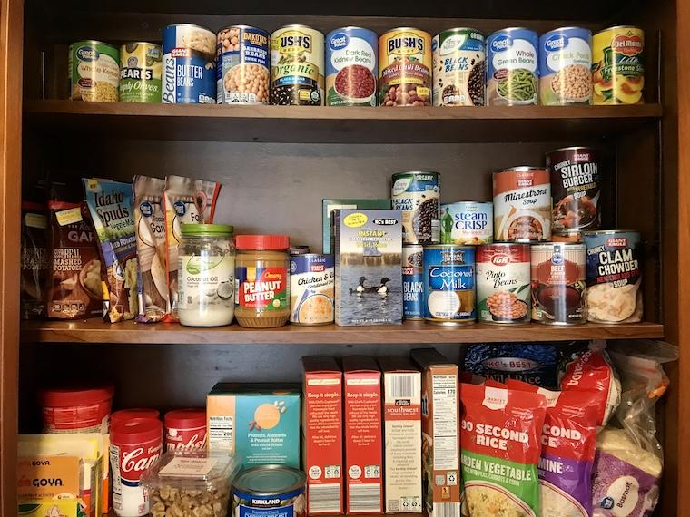 MRC Food Pantry with three shelves of canned goods, packaged foods and jars of sauces.
