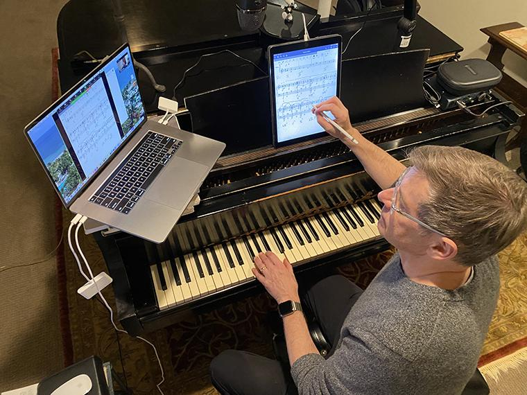 man sitting at the piano with laptop, iPad, and microphone