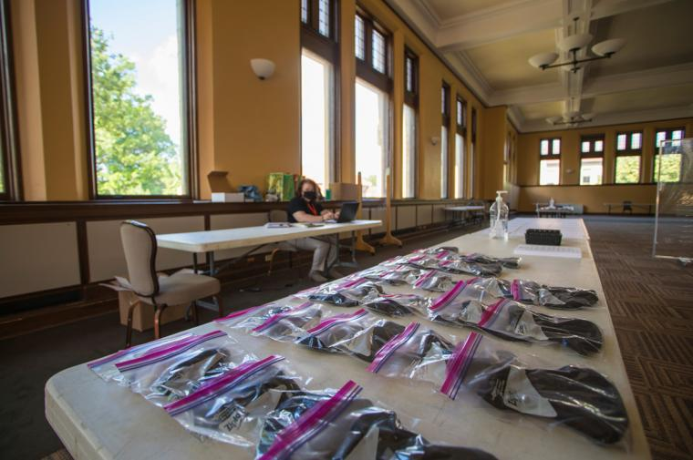 Masks in ziplock bags are laid out on a long table.
