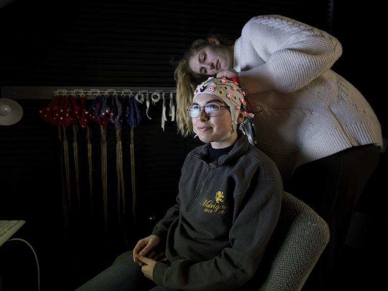 A in a white sweater adjusts an EEG cap on a student, who is seated in an office chair in front of a computer keyboard. The cap is off-white with pink and yellow nodes and wires coming out of it.