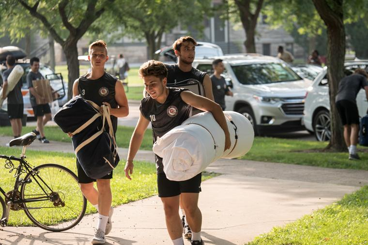 Students carrying luggage and bedding into a residence hall.