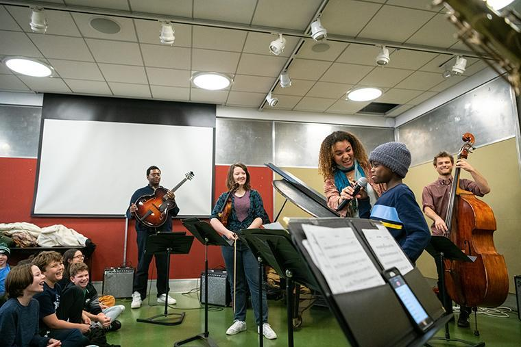 An Oberlin string quartet performs in front of a group of children. One of the musicians holds up a microphone to one of the children. They are smiling.