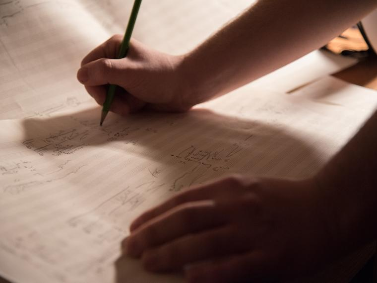 A person writing on a music score