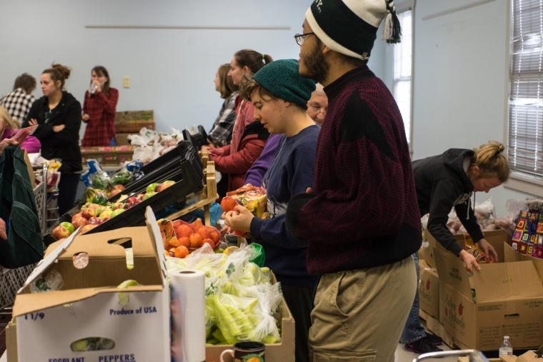 Several Oberlin students stand at a table filled with boxes of fresh fruits and vegetables, which are also piled on the floor behind the table. Individuals with shopping carts are lined up in front of the tables.