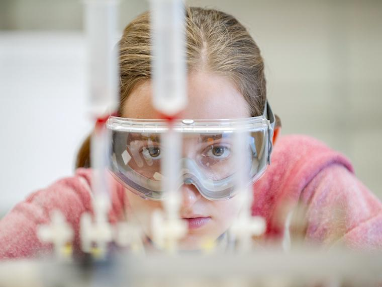 female student with science goggles looking straight at test tubes.