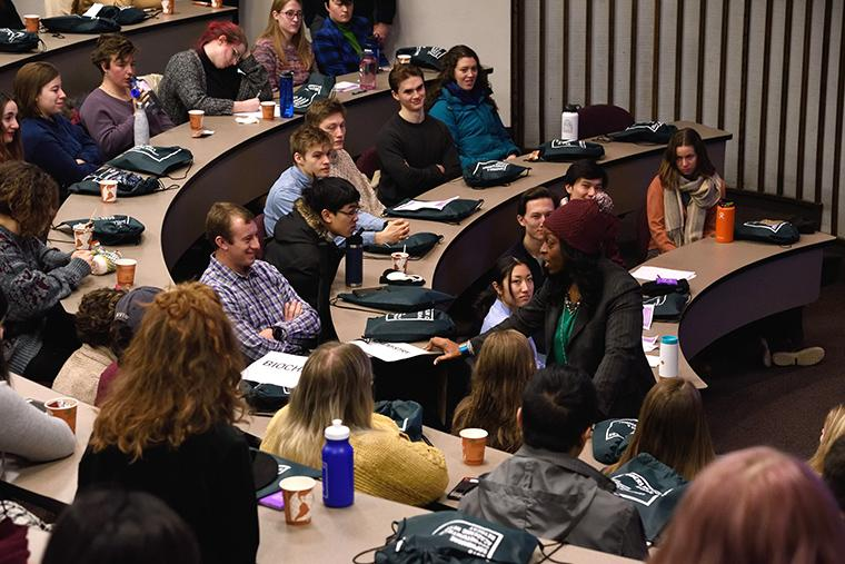 President Ambar engages with students in a lecture hall.