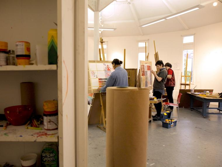 Photograph of art supplies and students working in an art studio.