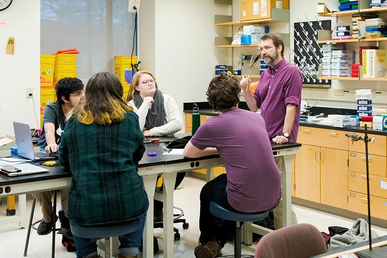 Four students and a professor have a conversation at a lab table.