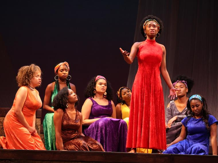 group of women on stage in different colored dresses