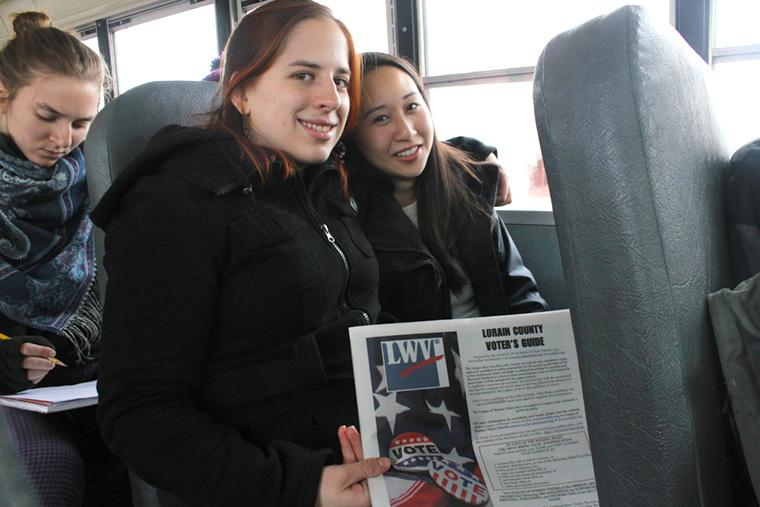 Two students seated on a bus, holding up a voting guide for Lorain County.